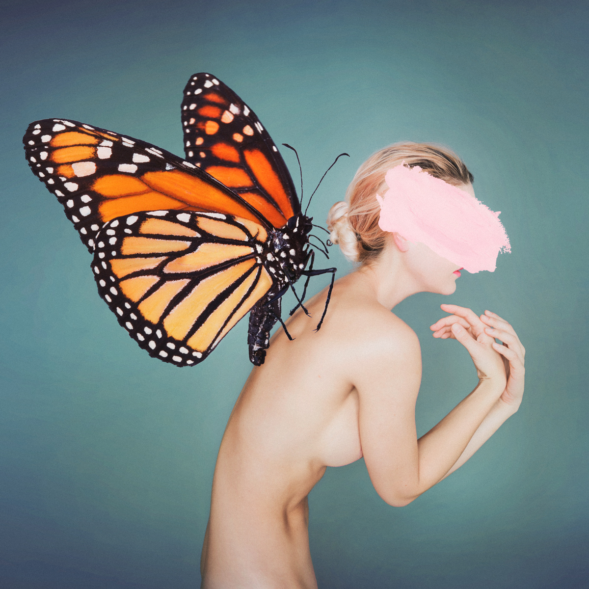 nude female with large orange  monarch butterfly on her back and a pink paint smudge across her face