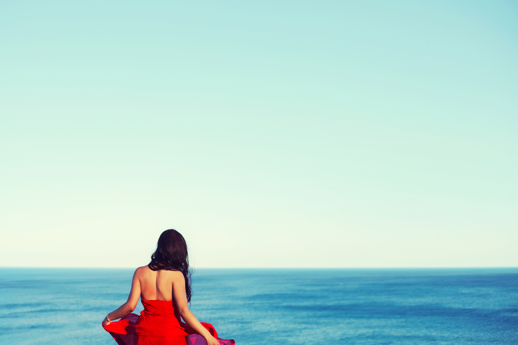 girl in red dress looking out at the blue water, lake ontario