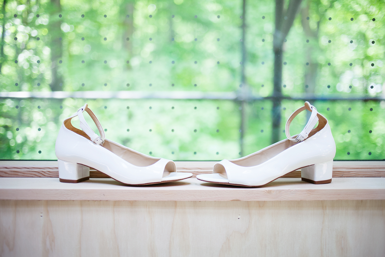 white bridal shoes in front of window